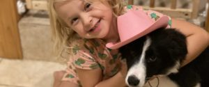 Blond girl holding black and white puppy with pink hat